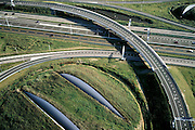 Nederland, Noord-Holland, Amsterdam-Zuidoost, 25-09-2002; knooppunt Holendrecht, het gereconstrueerde verkeersplein (A2 en A9) kent ook kunstwerken: de inkeping in de terp (linksonder), ontworpen door Dienst Ruimtelijke Ordening (DRO) en Ingenieurs Bureau Amsterdam (IBA); landart, fly-over, invoegstrook, spagetti, verkeer, autosnelweg;<br /> luchtfoto (toeslag), aerial photo (additional fee)<br /> foto /photo Siebe Swart