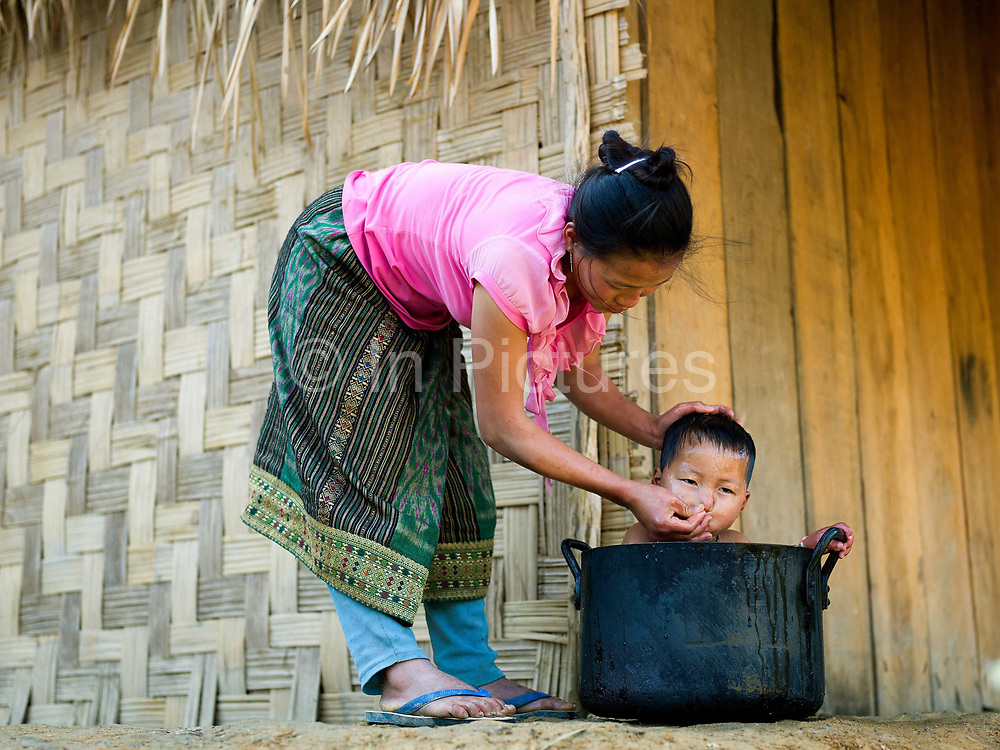 A Hmong ethnic minority woman washes her baby in a metal cooking pot, Ban Houaiyad, Houaphan province, Lao PDR