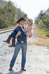 cowboy carrying a beautiful girl on a rural dirt road by railroad tracks