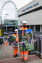 London, UK. 30th October, 2020. Activists dressed as HS2 workers arrive to take part in a HS2 Chainsaw Massacre protest outside the Among The Trees exhibition at the Hayward Gallery. The protest was intended to highlight deforestation, including the daily environmental destruction being wrought for the controversial HS2 high-speed rail project, and instances of violence and brutality by security guards and bailiffs working on behalf of HS2 Ltd.