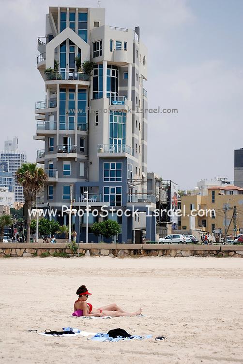 Israel, Tel Aviv, a woman sunbathing on the beach, a modern building on Trumpeldor street in the background