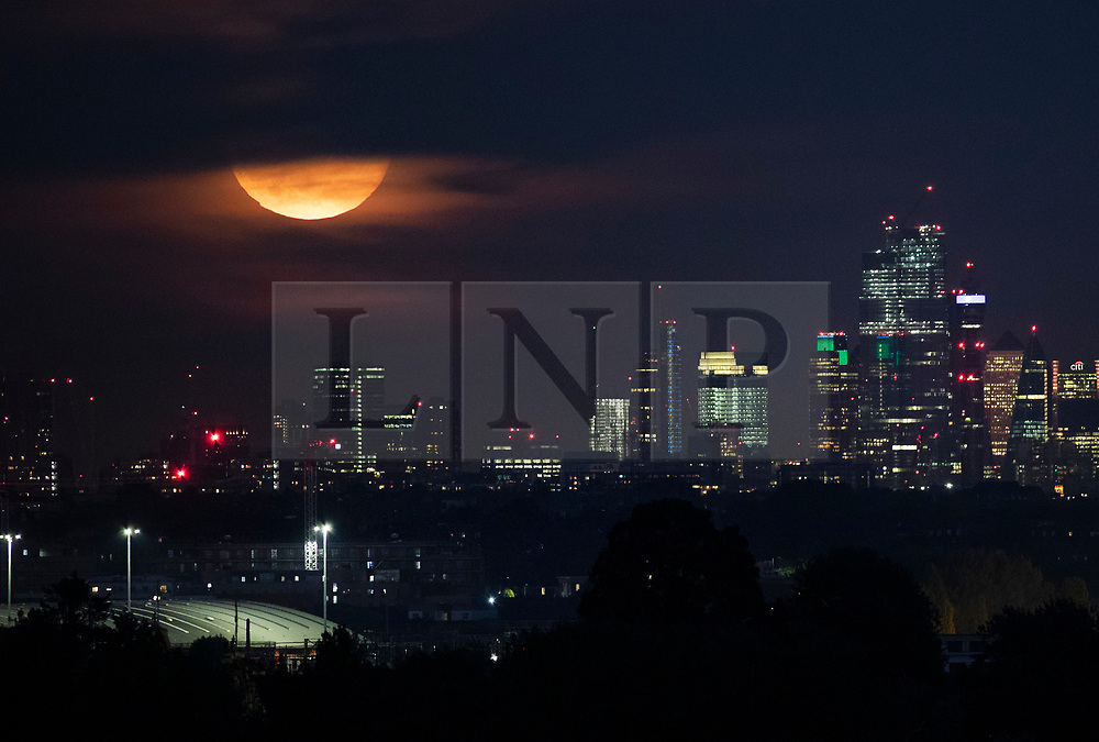 © Licensed to London News Pictures. 14/09/2019. London, UK. A partially obscured harvest full moon rises over the London Skyline. September's full moon is also a micro moon because it is furthest from Earth on it's eliptical orbit - appearing 14% smaller. Photo credit: Peter Macdiarmid/LNP