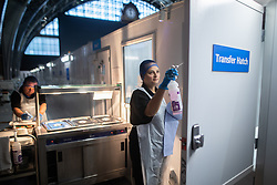 © Licensed to London News Pictures . 23/04/2020. Manchester, UK. Partners MIKE DELAHAY (42 - l) and VICKY ARMITT (37 - r - cleaning the transfer hatch) prepare lunch for patients on ward 7 of the hospital . The couple , who normally work alongside one another as cabin crew for Tui , originally volunteered to help whilst furloughed , but were put on staff by the hospital . The National Health Service has built a 648 bed field hospital for the treatment of Covid-19 patients , at the historical railway station terminus which now forms the main hall of the Manchester Central Convention Centre . The facility is treating patients from across the North West of England , providing them with general medical care and oxygen therapy after discharge from Intensive Care Units . Photo credit : Joel Goodman/LNP