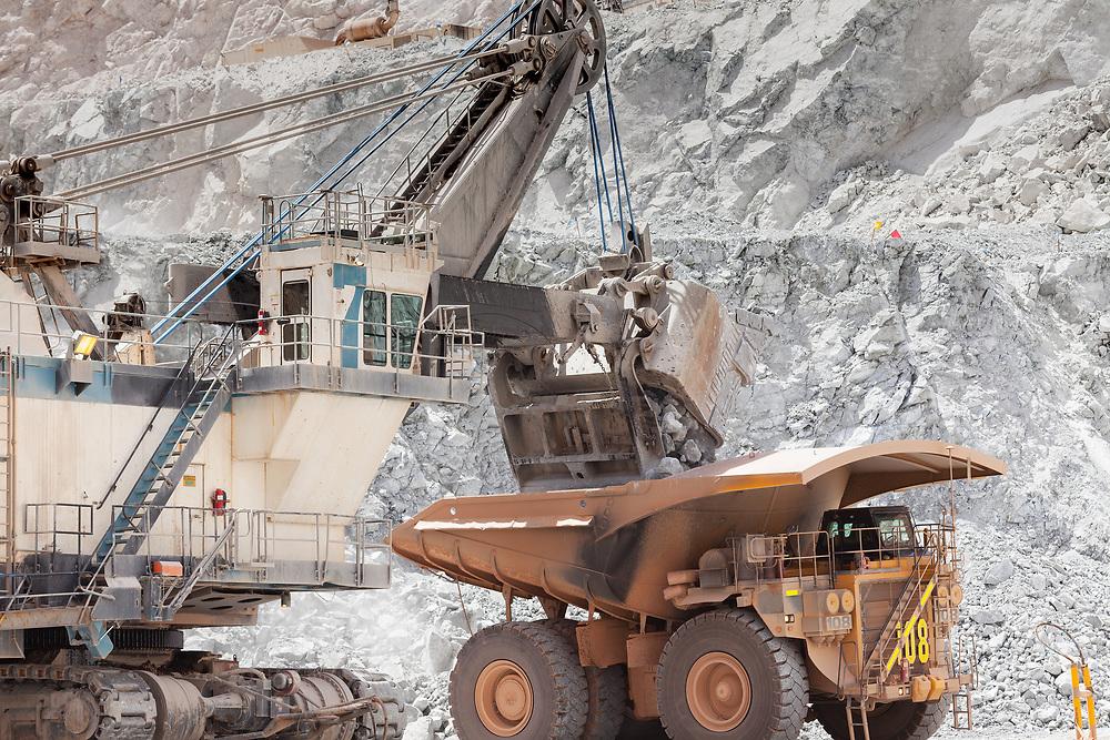 Electric rope shovel loading a dump truck at a copper mine in Peru