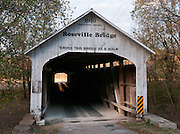 """Roseville Covered Bridge (263 feet long) was built in Burr Arch style over Big Raccoon Creek in 1910 by Van Fossen in Parke County, Indiana, The traditional """"Cross this bridge at a walk"""" sign requires slow vehicle speed. The """"light at the end of the tunnel"""" beckons."""