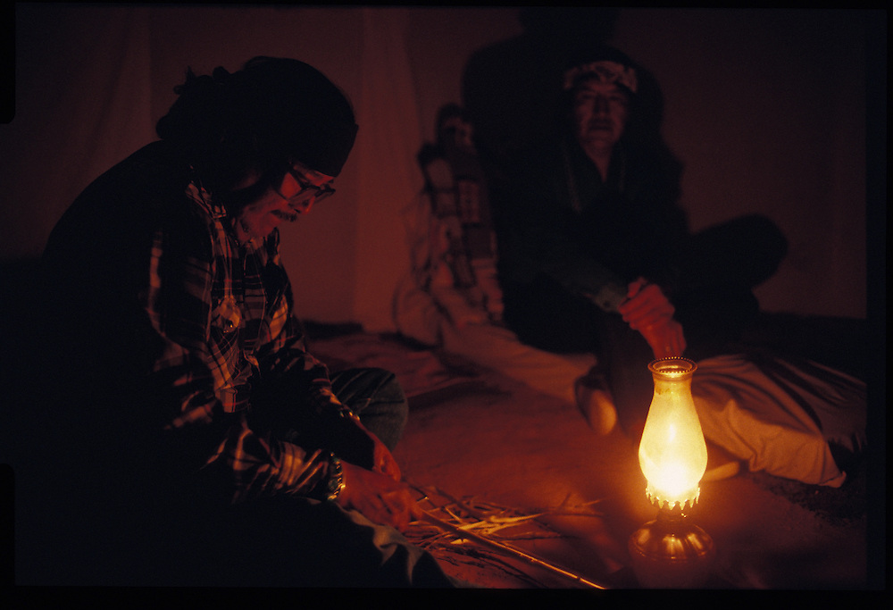 Medicine man Sam Begay and Paul Keams work by the light of a lamp during Keams' Balckening Way.