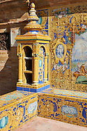 The tiled 'Province Alcoves' along the walls of the Plaza de Espana in Seville built in 1928 for the Ibero-American Exposition of 1929, Seville Spain . The Royal Alcázars of Seville (al-Qasr al-Muriq ) or Alcázar of Seville, is a royal palace in Seville, Spain. It was built by Castilian Christians on the site of an Abbadid Muslim alcazar, or residential fortress.The fortress was destroyed after the Christian conquest of Seville The palace is a preeminent example of Mudéjar architecture in the Iberian Peninsula but features Gothic, Renaissance and Romanesque design elements from previous stages of construction. The upper storeys of the Alcázar are still occupied by the royal family when they are in Seville. <br /> <br /> Visit our SPAIN HISTORIC PLACES PHOTO COLLECTIONS for more photos to download or buy as wall art prints https://funkystock.photoshelter.com/gallery-collection/Pictures-Images-of-Spain-Spanish-Historical-Archaeology-Sites-Museum-Antiquities/C0000EUVhLC3Nbgw <br /> .<br /> Visit our MEDIEVAL PHOTO COLLECTIONS for more   photos  to download or buy as prints https://funkystock.photoshelter.com/gallery-collection/Medieval-Middle-Ages-Historic-Places-Arcaeological-Sites-Pictures-Images-of/C0000B5ZA54_WD0s