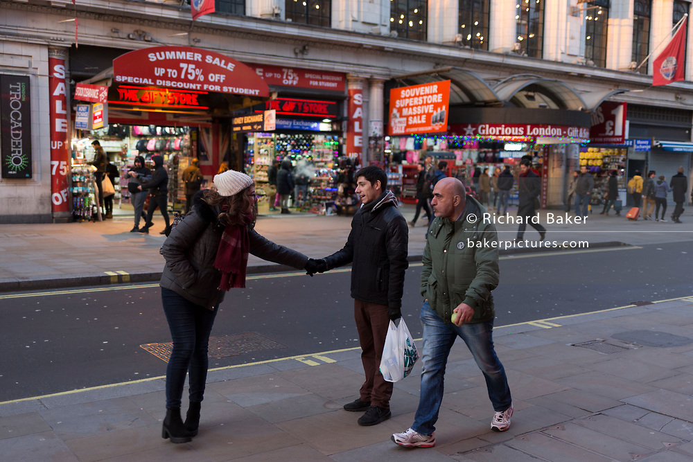 Friends reach out in the busy Coventry Street in London's West End, on 6th February 2018, in London, England.