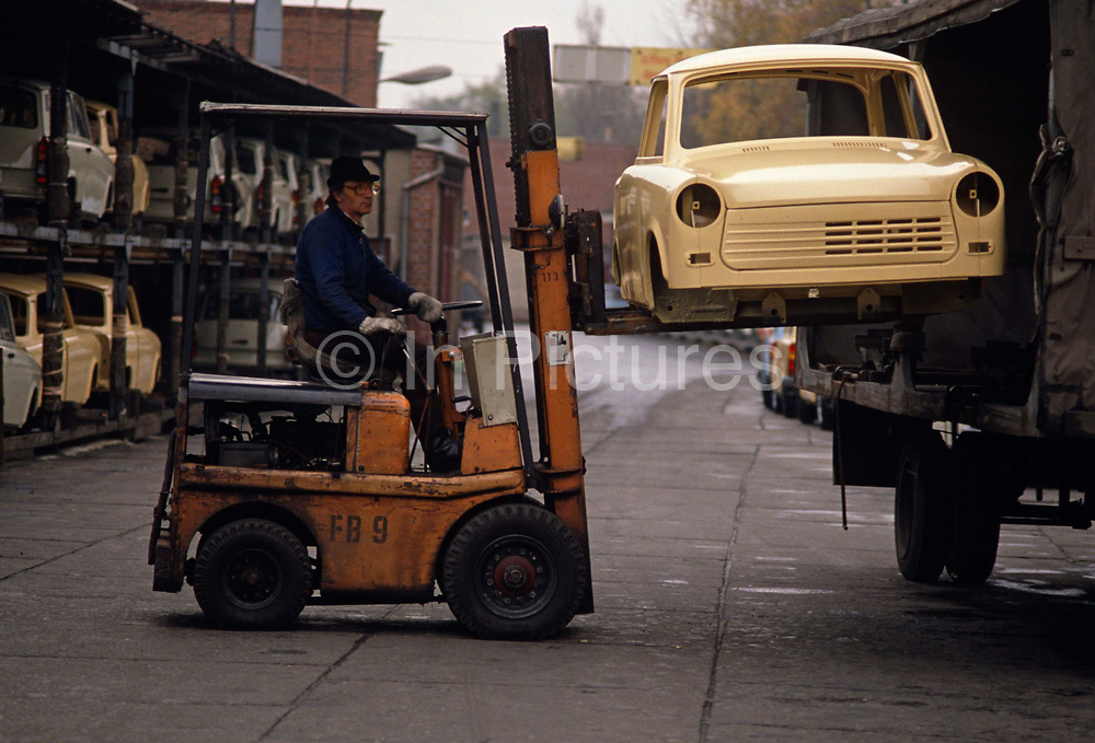 A new Trabant car shell is lifted by forklift from a truck at the East German auto maker VEB Sachsenring Automobilwerke Zwickau in Zwickau, Saxony.  A worker carefully manoeuvres the unfinished bodywork into a crate where other vehicles await completion on the production line. The Trabant was the most common vehicle in East Germany - Like the Beetle in the West, its Peoples' Car with a 595 cc, two-cylinder air-cooled engine. It had space for four, was compact, light and durable with its distinctive body shape constructed from Duroplast panels attached to a galvanized steel shell. It was in production without any significant changes for about 34 years, becoming a symbol for the cheap, cheerful and polluting possessions for Communist Europeans. When the Berlin Wall eventually fell, Trabants coughed and spluttered onto West German roads for the first time