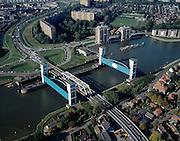 Nederland, Zuid-Holland, Capelle aan den IJssel, 08-03-2002; stormvloedkering in de Hollandsche IJssel. Bij storm en dreigend hoog water wordt een van de twee schuiven naar beneden gelaten, de tweede schuif dient al reserve. De scheepvaart kan de gesloten kering paseren via de naastgelegen schutsluis. De stormvloedkering maakt deel uit van de Deltawerken en is als eerste voltooid in 1958. Ten tijde van De Ramp - watersnood 1953 - werd het zeewater door de storm opgestuwd en dreigde de verzwakte rivierdijken in het achterland het te begeven waardoor grote van het laag gelegen westen van Nederland ondergelopen zouden zijn. De flats staan staan in Capelle a/d IJssel, rechtsonder Krimpen aan den IJssel..Netherlands, Capelle at the river IJssel, near Rotterdam: storm surge barrier, protects the highly populated western part of Holland, which lies below sea level. In case of storm and threat of high water, one of the two doors is lowered into the river (the second door is a spare one). The lock next to the barrier allows shipping when the barrier is closed...luchtfoto (25 procent toeslag); aerial photo (additional fee required)..foto Siebe Swart / photo Siebe Swart