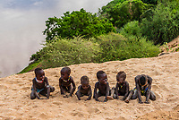 Kara tribe boys play at the edge of Dus village, overlooking the Omo River, Omo Valley, Ethiopia.