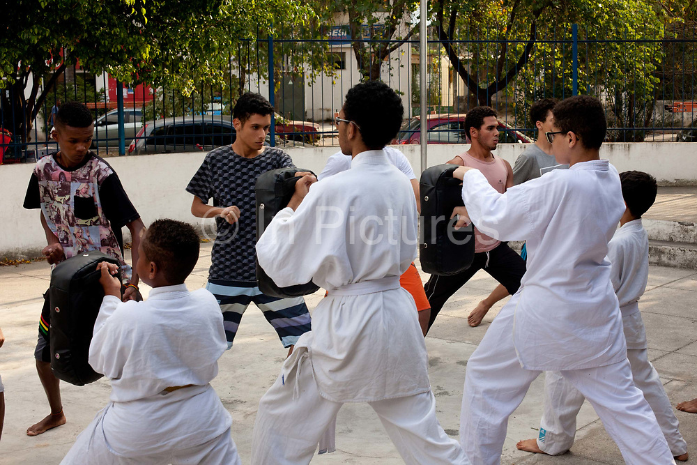 Young people train in a Karate school in City of God. Community projects like this are where many athletes from marginalised communities start their careers, such as Rafaella Silva - Brazils Olympic Judo Gold Medalist, who is from this community. Cidade de Deus / City of God favela in Rio de Janeiro, made infamous by the film of the same name, is a bustling community of close to 100,000 inhabitants, with numerous cultural and social projects.