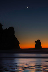 Crescent moon and sunset at Morro Rock in Morro Bay California