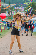 An Asian woman dances up the hill to the camp site - The 2017 Glastonbury Festival, Worthy Farm. Glastonbury, 2 June 2017