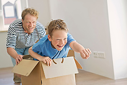 Father son new apartment playing cardboard box