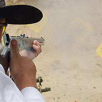 Competitor fires his weapon during the Cowboy Action Shooting European Championship in Dabas, Hungary on August 11, 2012. ATTILA VOLGYI