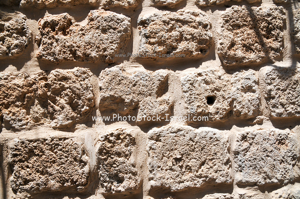 Close up of a wall constructed from crude bricks of Kurkar a calcareous sandstone or fossilized sea sand dunes common in Israel. Photographed in Acre