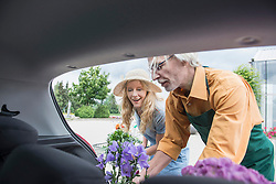 Shop assistant helping a customer putting plant in a car trunk, Augsburg, Bavaria, Germany