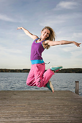 Woman dancing Zumba on jetty, Woerthsee, Bavaria, Germany