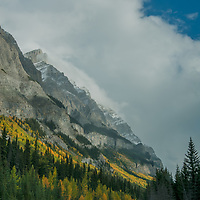 After a rain squall, cars drive below the Canadian Rockies on the Icefields Parkway.
