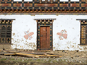 A farmhouse In Yangthang village in the Haa valley, Western Bhutan. A typical Bhutanese house is two storeys high with a large airy attic used for storage. In rural areas the ground floor is always used as a barn and the upper floor as the living quarters. In most houses, one elaborately decorated room called the 'choesum' serves as a chapel. In Western Bhutan the walls are usually made of compacted earth. Afterwards the walls are whitewashed and painted decorations added. Phallic decoration is believed to ward off evil spirits and encourage fertility.