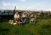 Family picnic sitting in camping chairs in field next to car, Stumps Cross, North Yorkshire, England in 1963