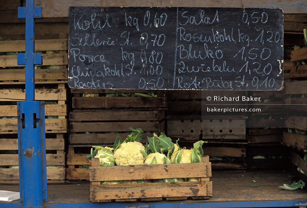 A year after the fall of the Berlin Wall and the end of the Communist Eastern Bloc, a wooden crate of cauliflowers are displayed underneath the prices of other vegetables at a street market in Leipzig in eastern Germany, on 4th November 1990, in Leipzig, Germany.