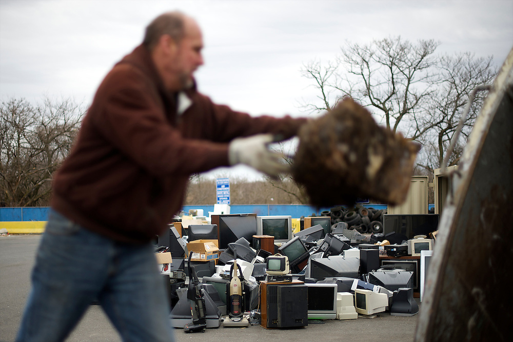 Mike Horgan of Philadelphia throws yard debris into a garbage truck at the Torresdale Convenience Center, while hundreds of television sets and assorted electronics are piled in background, in Philadelphia, PA on February 26, 2013.