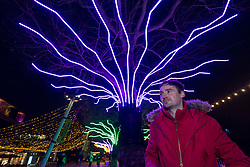 "© Licensed to London News Pictures. 07/12/2020. LONDON, UK. Artist David Ogle in front of his work ""Lumen"", trees illuminated with glowing neon flex. Preview of ""Winter Light"" presented by Southbank Centre.  Over 15 artworks and new illuminated commissions by a range of leading international artists are on display around the site's buildings and the Riverside Walk until the end of February 2021.  Photo credit: Stephen Chung/LNP"