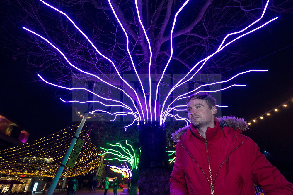 """© Licensed to London News Pictures. 07/12/2020. LONDON, UK. Artist David Ogle in front of his work """"Lumen"""", trees illuminated with glowing neon flex. Preview of """"Winter Light"""" presented by Southbank Centre.  Over 15 artworks and new illuminated commissions by a range of leading international artists are on display around the site's buildings and the Riverside Walk until the end of February 2021.  Photo credit: Stephen Chung/LNP"""