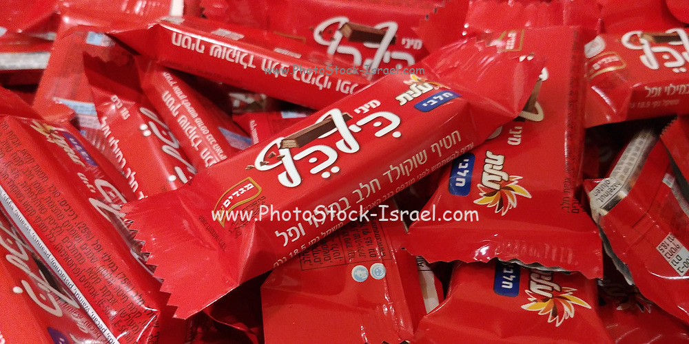 A large stack of KifKef Israeli mini wafer coated Chocolate bars with Hebrew text