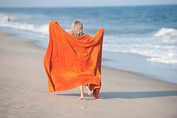 girl walking down the beach in East Hampton with an large orange towel
