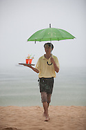 A hotel staff delivers drinks to guests during a downpoor. Phu Quoc island, Vietnam, Southeast Asia