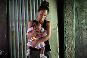 Myleene Klass, a celebrity from the UK, holds Jihan, aged 4 months, who has been formula-fed since birth despite the poverty of his mother, Josephine Savares, 18, in Paranaque, Metro Manila, The Philippines on 19 January 2013. Josephine had decided to feed her baby formula during her pregnancy and had no idea that her father had to pay such a high price for it. Her family goes without food some days, and her siblings have had to stop school in order to afford the formula. Photo by Suzanne Lee for Save the Children UK