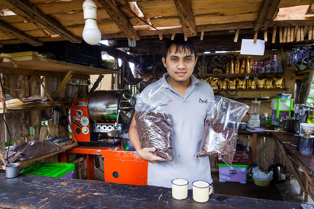 Shahiru Lur Imam (24) makes fresh coffee at his cafe located at his father's coffee farm associated with KBQB.  Shahiru's father, Pak Salmy (53), has made his coffee farm as a tourist attraction, Galeri Kopi Indonesia, where visitors could learn the process of farming coffee, barista training, roasting, and tasting, and to visit and enjoy a fresh cup.