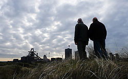 © Licensed to London News Pictures.20/10/15<br /> Redcar, UK. <br /> <br /> Two men stand on the dunes and look out over the recently closed SSI UK steel blast furnace in Redcar, England. The closure of the site marks the end of 170 years of steel making heritage on Teesside and was the first of a number of recent closures of steel making plants across the UK.<br /> <br /> Photo credit : Ian Forsyth/LNP
