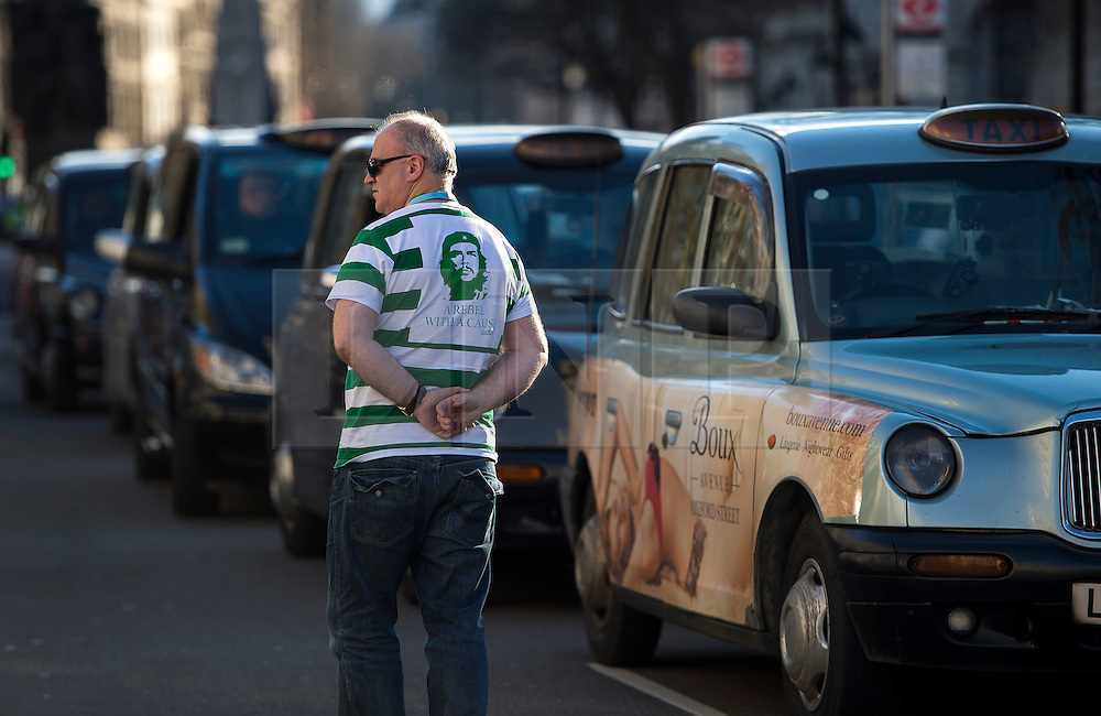 """© Licensed to London News Pictures. 10/02/2016. London, UK. A cab driver wearing a t-shirt reading """"REBEL WITH A CAUSE"""" as thousands of London black cab drivers stage a protest in Westminster, London against Government interference in the taxi industry and 'active support' for Uber, which they allege is a 'tax avoiding global corporation' Photo credit: Ben Cawthra/LNP"""