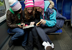 Teenage Girls Sitting on Train Inspecting a Guidebook