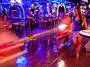 "12 JULY 2011 - BANGKOK, THAILAND: A Thai woman walks in the rain past a beer bar frequented by prostitutes and their customers on Soi Cowboy, a ""red light"" district in Bangkok. Prostitution in Thailand is illegal, although in practice it is tolerated and partly regulated. Prostitution is practiced openly throughout the country. The number of prostitutes is difficult to determine, estimates vary widely. Since the Vietnam War, Thailand has gained international notoriety among travelers from many countries as a sex tourism destination. One estimate published in 2003 placed the trade at US$ 4.3 billion per year or about three percent of the Thai economy. It has been suggested that at least 10% of tourist dollars may be spent on the sex trade. According to a 2001 report by the World Health Organisation: ""There are between 150,000 and 200,000 sex workers (in Thailand).""  PHOTO BY JACK KURTZ"