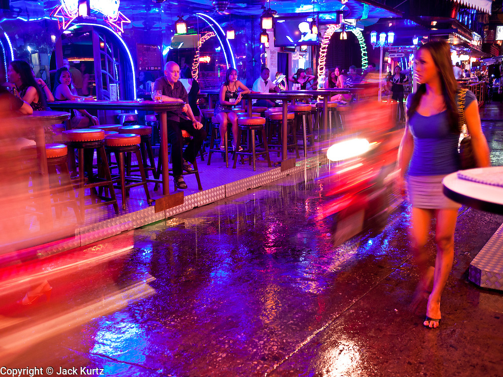 """12 JULY 2011 - BANGKOK, THAILAND: A Thai woman walks in the rain past a beer bar frequented by prostitutes and their customers on Soi Cowboy, a """"red light"""" district in Bangkok. Prostitution in Thailand is illegal, although in practice it is tolerated and partly regulated. Prostitution is practiced openly throughout the country. The number of prostitutes is difficult to determine, estimates vary widely. Since the Vietnam War, Thailand has gained international notoriety among travelers from many countries as a sex tourism destination. One estimate published in 2003 placed the trade at US$ 4.3 billion per year or about three percent of the Thai economy. It has been suggested that at least 10% of tourist dollars may be spent on the sex trade. According to a 2001 report by the World Health Organisation: """"There are between 150,000 and 200,000 sex workers (in Thailand).""""  PHOTO BY JACK KURTZ"""