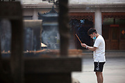 A man praying and burning incense in the Jing'an Temple courtyard , Shanghai, China
