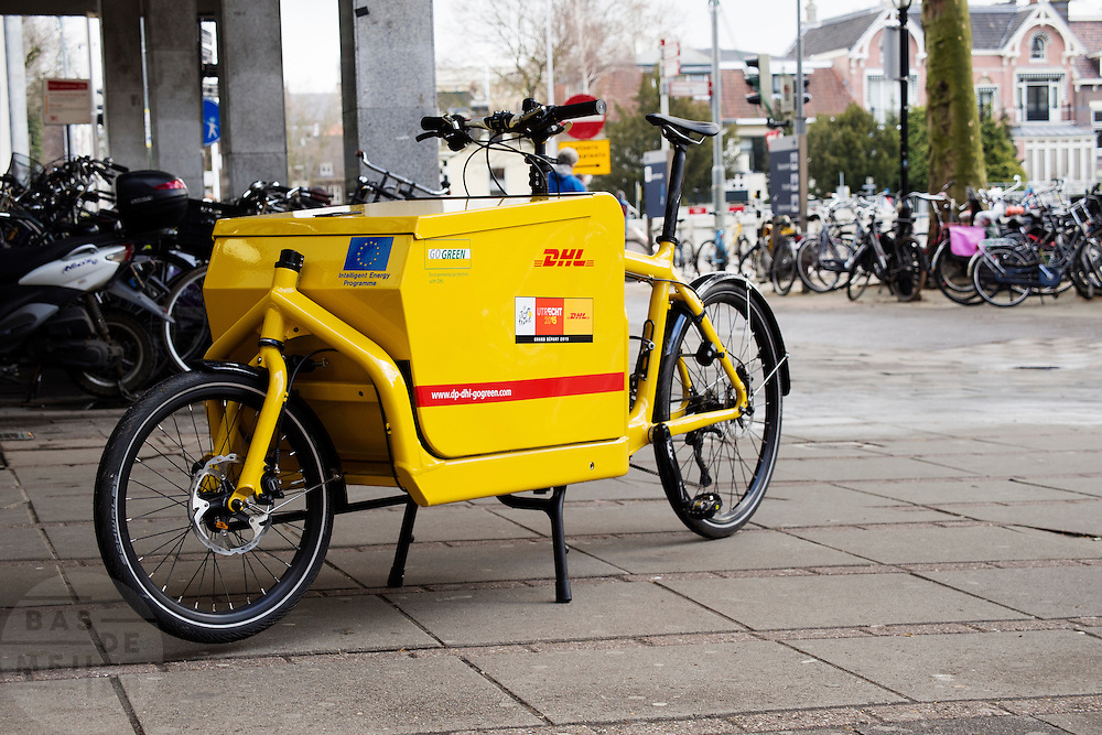 In Utrecht staat voor de ingang van winkelcentrum Hoog Catherijne een bakfiets van DHL.<br /> <br /> In Utrecht a DHL cargo bike is parked at the entrance of shopping center Hoog Catherijne.