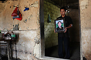 Ouyang Guoping holds a picture of his deceased brother, Ouyang Muzhi, who died from unexplained illnesses, at their home in Shuangqiao Village, Hunan Province, China on 13 August 2009.  The nearby Xianghe chemical plant has been shut down on suspected inadequate waste treatment that may have led to water and soil contamination that caused illness and death within the village of Shuangqiao.