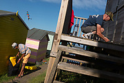 As a neighbour packs away beach equipment, another ensures that all doors and locks are secured on a beach hut on the seaside promenade, on 18th July 2020, in Whitstable, Kent, England.