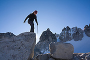 Climber Grace Marx stands on a large boulder with her ice axe preparing to jump near Colchuck Lake below Dragontail Peak, Alpine Lakes Wilderness, Washington.