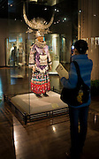 Visitor looks at Chinese costume and Miao silver jewellery on display in glass case at the Shanghai Museum, China
