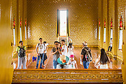 16 JULY 2014 - SAMUT PRAKAN, SAMUT PRAKAN, THAILAND: Tourists walk through a reconstruction of the Sanphet Prasat Throne Hall from Ayutthaya at Ancient Siam. The original was destroyed by the Burmese when they ransacked Ayutthaya in 1767. Ancient Siam is a historic park about 200 acres (81 hectares) in size in the city of Samut Prakan, province of Samut Prakan, about 90 minutes from Bangkok. It features historic recreations of important Thai landmarks and is shaped roughly like the country of Thailand.      PHOTO BY JACK KURTZ