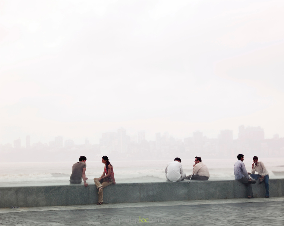 Mumbai locals sit on a sea wall in the rain during the monsoon season, Mumbai, India