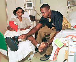 23 September 2001. Bellevue Hospital, New York City, New York, USA.<br /> Genelle Guzman-McMillan - nee Genelle Guzman. Aftermath of 9/11 Terrorist attack on World Trade Centre.<br /> Last known survivor.<br /> 23 September 2001; Bellevue Hospital, New York City, New York, USA.<br /> Genelle Guzman-McMillan - nee Genelle Guzman. Aftermath of 9/11 Terrorist attack on World Trade Centre.<br /> Last known survivor.<br /> Gentle Guzman has a bandage applied to her ankle by her boyfriend Roger McMillan at Bellevue hospital as she recovers from being trapped in the rubble of the World Trade Centers debris. Gentle was trapped for 27 hours, pinned by heavy debris after the buildings collapsed around her killing her work colleagues. By some miracle Genelle attributes to God she was spared. Gentle was found by a German Shepherd rescue dog named Trakr and his handler James Symington.<br /> Genelle was told she would never recover from the crushing injuries to her legs, however she has since overcome the odds and went on to marry her sweetheart Roger McMillan who cared for in hospital throughout her ordeal.  <br /> Photo©; Charlie Varley/varleypix.com