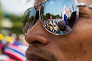 """09 DECEMBER 2013 - BANGKOK, THAILAND: Other anti-government protestors are reflected in the sunglasses of a protestor at Government House in Bangkok. Thai Prime Minister Yingluck Shinawatra announced she would dissolve the lower house of the Parliament and call new elections in the face of ongoing anti-government protests in Bangkok. Hundreds of thousands of people flocked to Government House, the office of the Prime Minister, Monday to celebrate the collapse of the government after Yingluck made her announcement. Former Deputy Prime Minister Suthep Thaugsuban, the organizer of the protests, said the protests would continue until the """"Thaksin influence is uprooted from Thailand."""" There were no reports of violence in the protests Monday.      PHOTO BY JACK KURTZ"""